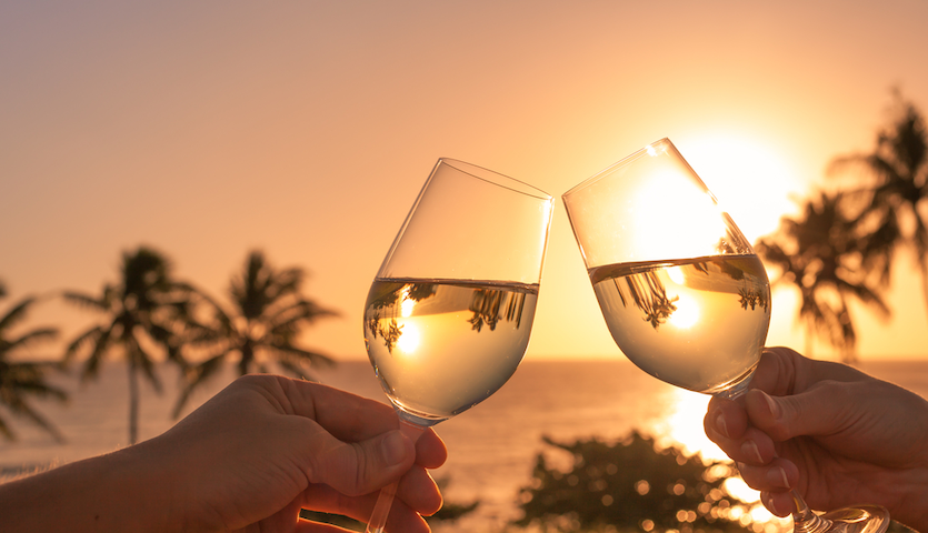 Drinking wine at sunset and clinking glasses