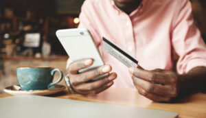 Man in coffee shop pays for something on his phone using a credit card
