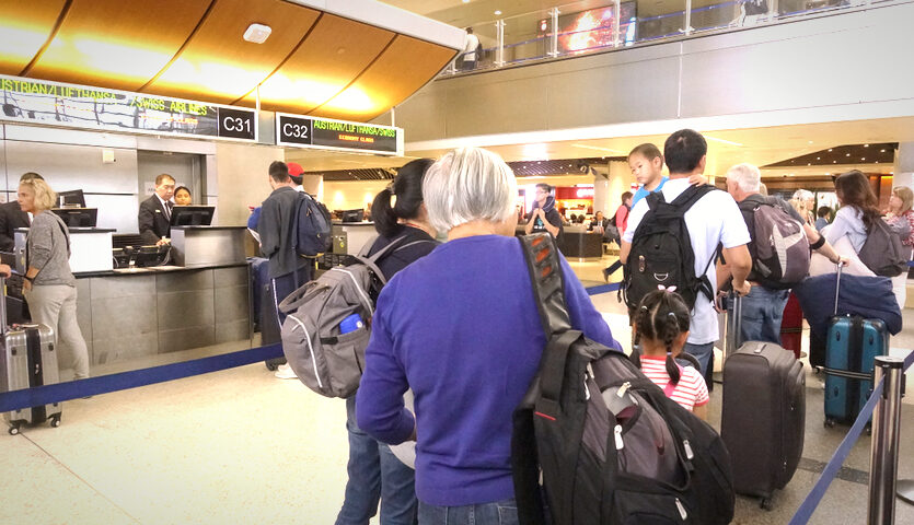 people wait in line at airline check-in ticket counter