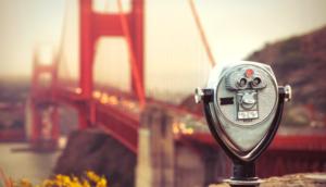 tower viewer tourist binoculars in foreground with san francisco golden gate bridge blurred in background