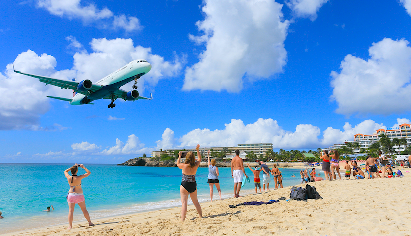 People watching planes touchdown in St. Maarten Maho Beach