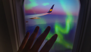 hand on the window of icelandair plane with northern lights outside