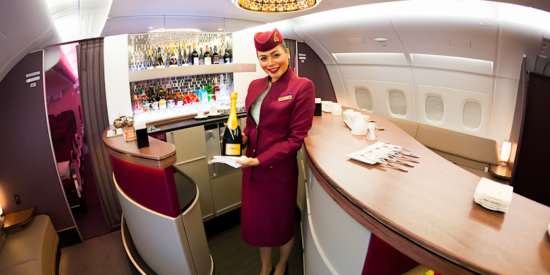 Qatar Airways flight attendant in business class bar with champagne