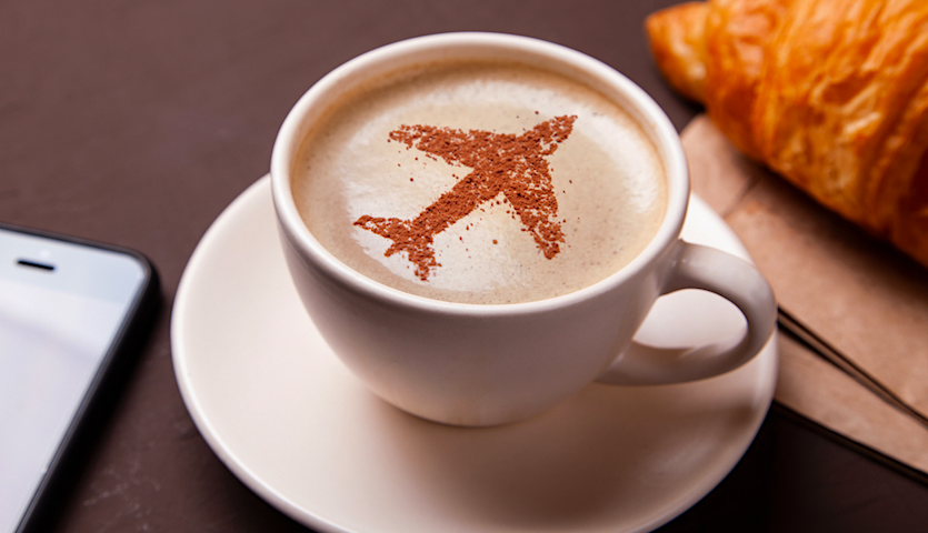 Mug of coffee with airplane image in foam