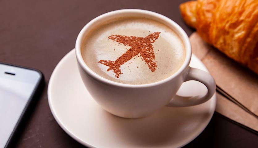 Mug of coffee with airplane image in foam