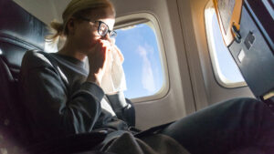 blonde-caucasian-woman-sneezing-on-airplane