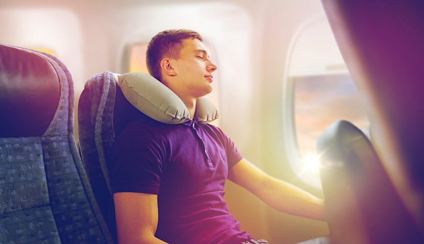 man sleeping on airplane with neck pillow