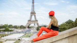 Woman looks out at the Eiffel Tower while wearing a red beret.
