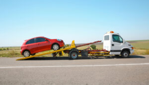 Red-car-on-tow-truck-on-highway