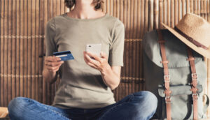 woman on vacation makes credit card purchase on her smartphone