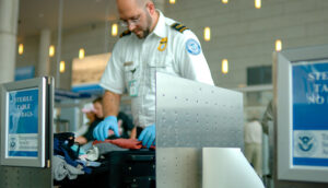 A TSA agent searches luggage at an airport.