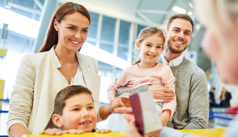 familly with children checking in at the airport counter