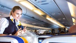 flight attendant speaking with passengers on flight plane; RUBEN M RAMOS/Shutterstock