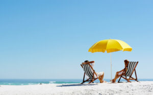 Couple relaxes in beach chairs under umbrella on beach