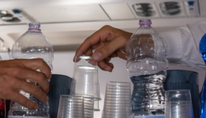 Flight attendants prepare cups of water for passengers