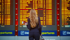 woman at flight board looking at cancelled flights