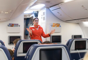 Flight attendant demonstrates where exits are located on flight
