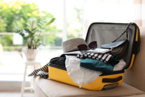 yellow suitcase overflowing with clothes